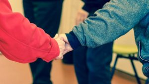 Two senior citizens holding hands in the care home