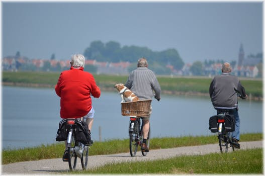 Three senior citizens riding bikes as part of their elderly care social activities