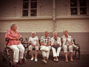 Five older women meeting for a social visit as part of their elderly are regime