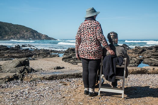 Woman who takes care of elderly people standing next to senior friend as she sits on the beach